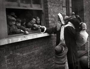 Babbo Natale consegna i regali per aiutare i bambini e le Adoption Society a Leytonstone, Londra. (Photo by Fox Foto - Getty Images). 20 novembre 1931